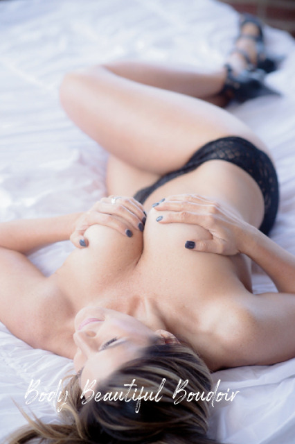 Woman lying in be with just black heels, panties and hand bra