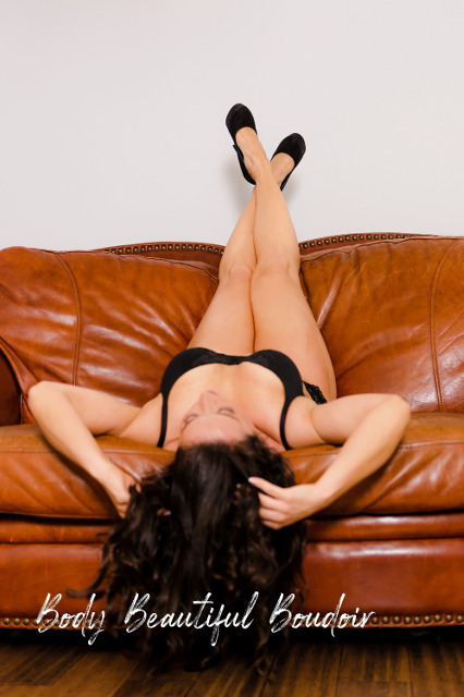 Posing on a leather couch in black bra and panties